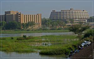 Le quartier de Gaweye à Niamey. J'ai vu ces bâtiments sortir de terre dans le début des années 80. C'est toujours beaucoup d'émotion et de souvenirs qui ressurgissent quand je les revois.  Remarquez en bas à droite de l'image les laveurs de linge.  Le sable en suspension dans l'air, phénomène fréquent dans le sahel, brouille un peu le ciel et l'arrière plan.